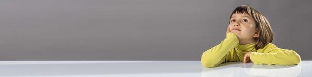 Длинное знамя с большим воображением ребенка смотря прочь для любопытства ребенк Стоковое Фото