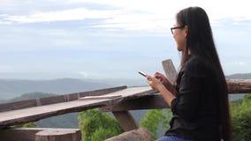 Длинные женщины черных волос азиатские нося стекла для игры черни или смартфона в предпосылке взгляда сверху леса горы