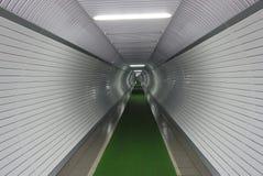 Длинный белый коридор в подвале с зеленым путем на плитке, загоренной лампами дневного света Стоковые Изображения