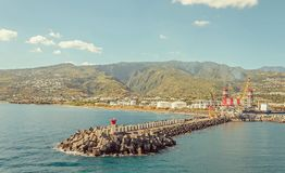 Длинный волнорез в порте и больших зеленых холмах Стоковое Фото