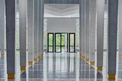 Длинный коридор между много столбцов, открыть двери в конце, симметричная современная зала стоковые фотографии rf