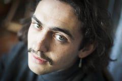 Длинный с волосами молодой человек с портретом усика и серьги стоковые фото