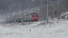 Длинный товарный состав приходя на железную дорогу в зиме сток-видео