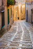 Длинняя улица булыжника в Erice, Сицилии, Италии, на заходе солнца Стоковое Изображение RF
