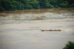 Длинн-замкнутая шлюпка с полными пассажирами бежит agai в верхней части потока Стоковое Изображение