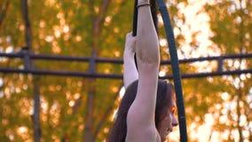 Длинн-с волосами девушка льнет к кольцу для воздушной акробатики, замедленному движению акции видеоматериалы