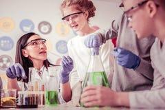 Длинн-с волосами женщина экспериментируя с химикатами со студентами рядом стоковые изображения rf