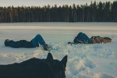 Для девушек лежа в собаке снега наблюдая стоковое изображение