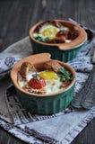 Для завтрака, яичко с хлебом и вся вишня томатов испекли в прессформах печи стоковое фото rf