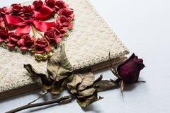 Дневник и розы влюбленности вянут на белой предпосылке холста Стоковая Фотография