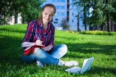 Дневник сочинительства девочка-подростка в парке Стоковое Фото