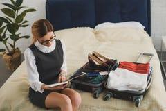 дневник чтения коммерсантки пока пакующ чемодан стоковая фотография