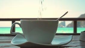 Добавление сахара к кофе в стеклянной кружке с видом на море видеоматериал