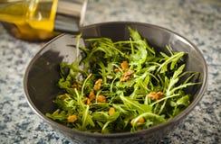 Добавлять оливковое масло к arugula и салату гаек Стоковые Изображения