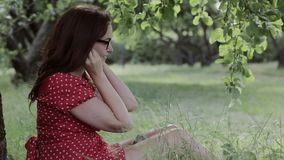 Добавочная девушка размера сидя на траве под деревом и слушая к музыке, используя ее смартфон сток-видео