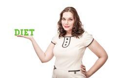 Добавочная женщина размера представляя диету слова на ее ладони стоковое изображение rf