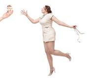 Добавочное желание женщины размера для торта с сантиметром в руках стоковая фотография