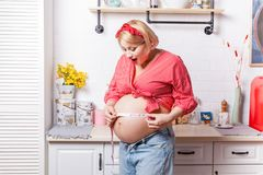 Добавочный размер Приятный удивленный тип измерения удерживания беременной женщины и использование его на ее животе пока выражающ стоковое изображение