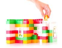 добавьте руку здания кирпича к игрушке Стоковая Фотография