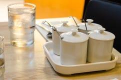 Добавьте чашку Condiments и выпивая стекло Стоковое Изображение