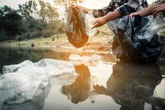 Добровольная рудоразборка вверх пластмасса бутылки в реке стоковое изображение