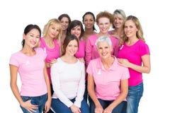 Добровольные жизнерадостные женщины представляя и нося пинк для canc груди Стоковая Фотография RF
