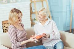 Добросердечная внимательная бабушка давая симпатичный настоящий момент к ее внуку Стоковое фото RF