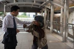 Добросердечный бизнесмен дает деньги к бездомные как Стоковое фото RF