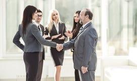 Добро пожаловать и рукопожатие деловых партнеров на предпосылке аплодируя работников Стоковое Фото