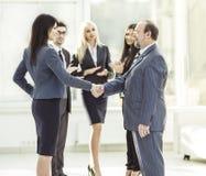 Добро пожаловать и рукопожатие деловых партнеров на предпосылке аплодируя работников Стоковая Фотография