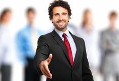Добро пожаловать в команду: бизнесмен давая его руку стоковое изображение rf
