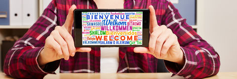 Добро пожаловать в различных языках на smartphone Стоковое Фото