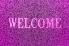 Добро пожаловать фиолетовый коврик у входной двери Добро пожаловать предпосылка ковра стоковая фотография rf