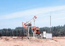 Добыча нефти, нефтяная скважина стоит на поле среди леса, голубого неба, извлечения нефти стоковые фотографии rf