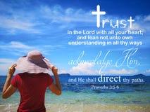 Доверие в боге с видом на океан предпосылки и дама смотрят до дизайн неба для христианства стоковые фото