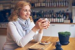 Довольная зрелая женщина наслаждаясь чашкой чаю Стоковое Изображение RF