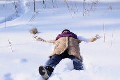 Довольная кавказская женщина идет в парк зимы Молодая женщина против покрытого снег парка на солнечный день стоковая фотография