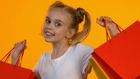 Довольная маленькая девочка показывая красные хозяйственные сумки на камере и усмехаясь, продажи видеоматериал