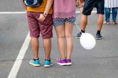 Довольное молодые люди с воздушным шаром в их руках стоя на улице Только ноги видимые задний взгляд стоковые изображения rf