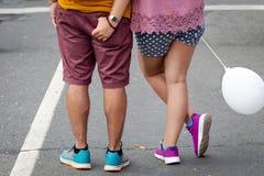 Довольное молодые люди с воздушным шаром в их руках стоя на улице Только ноги видимые задний взгляд стоковые фото