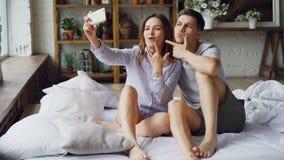 Довольно азиатская девушка принимает selfie при ее красивый кавказский парень держа smartphone представляя и целуя романтично видеоматериал
