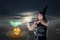 Довольно азиатская женщина ведьмы показывает ей волшебную силу палочки Стоковое Фото