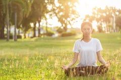 Довольно азиатская женщина делая йогу работает в парке стоковые фотографии rf