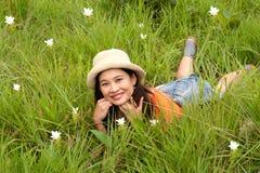 Довольно азиатская женщина лежа на поле цветка. стоковая фотография rf
