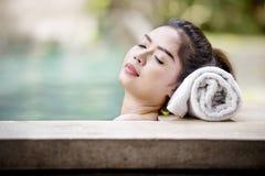 Довольно азиатская женщина лежа на poolside стоковое изображение