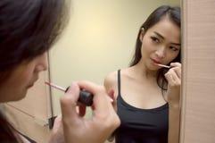 Довольно азиатская женщина на зеркале красит губы с красной губной помадой Стоковые Фото