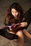 Довольно азиатская книга чтения женщины на гамаке. Стоковые Фото