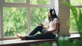 Довольно азиатский студент наслаждается музыкой в наушниках сидя на силле окна и используя экран smartphone касающий самомоднейше видеоматериал