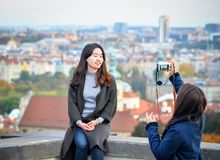 2 довольно азиатских девушки принимают selfie и смотрят старый город Праги от смотровых площадок около замка Праги, Праги Стоковое фото RF