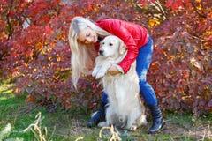 Довольно белокурая девушка идя с собакой в концепции животного леса Стоковые Фотографии RF
